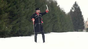 A young man in Cossack clothes swinging a sword in a winter landscape in the snow. stock footage