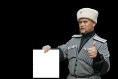 Young man in a cossack clothes with Thumb Up. Young cossack with Thumb Up on a black background Royalty Free Stock Photos