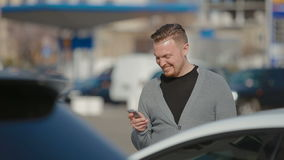 The young man costs on the parking and prints SMS stock video footage