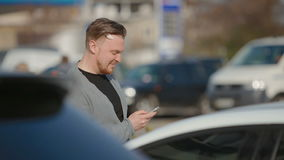 The young man costs on the parking and something looks in phone. stock video
