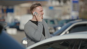 The young man costs on the street and emotionally speaks by phone stock video footage
