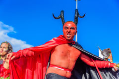 Young man in a costume of devil with red face, black horns and cloak walking on stilts at Bloco Orquestra Voadora, Carnaval 2017 Stock Photos