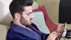Young man on couch reading with tablet PC stock video footage