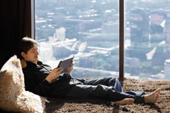 Young man on couch with tablet Stock Photography