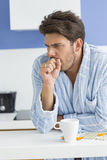 Young man coughing with coffee mug and medicine on kitchen counter. Young men coughing with coffee mug and medicine on kitchen counter Stock Photography