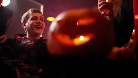 Young man in Count Dracula`s costume sits surrounded by friends in a dark cafe stock footage