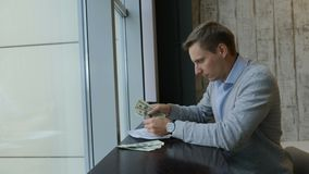 Young man counting US dollars. Business life concept. Big panoramic window. lifestyle. Shot in 4 k. Young man counting US dollars. Business life concept. Big stock video