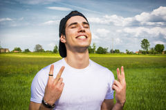 Young man at countryside, doing victory sign Stock Images