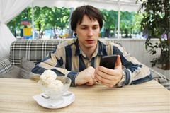 A young man counts with a smartphone the calorie content of ice cream. diet and applications for the smartphone help look good. th Stock Image