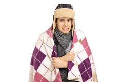 Young man covered with a blanket feeling cold. Isolated on white background Royalty Free Stock Photo