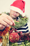 Young man covered with christmas ornaments Royalty Free Stock Photos