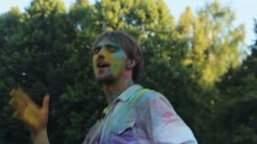 Young man covered in colored paint dancing and having fun at Holi festival. Stock footage stock video