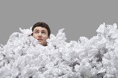 Young Man Covered In Crumpled Papers. Looking up against gray background Stock Photography