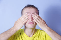 Young man covered eyes. Do not see. Royalty Free Stock Image
