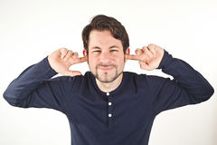 Young man covering ears from loud noise, isolated on white backg Stock Images
