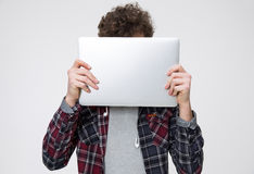 Young man covering face with laptop. Over gray background Stock Images