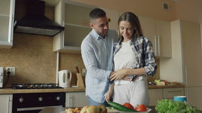 Young man covering girlfriends eyes with hands and surprising her in the kitchen at home. Loving couple cooking breakfast in the morning stock footage