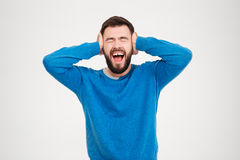 Young man covering his ears and screaming Stock Photography
