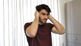 Young man covering his ears, too much noise. Handsome young man covering his ears, stressed or unhappy because of too much noise. Indoors shot stock photos