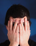 Young man covering his eyes Royalty Free Stock Images