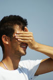 Young man covering his face Stock Image