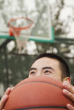 Young man covering his face with basketball Royalty Free Stock Photos
