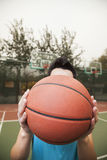 Young man covering his face with basketball, portrait Stock Photos