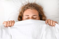 Young man covering his face with blanket while sleeping on pillow stock image
