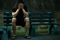 Depressed man sitting on a park bench covering his face with his hands royalty free stock photos