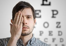 Young man is covering his face with hand and checking his vision. Chart for eye sight testing in background.  Royalty Free Stock Photo
