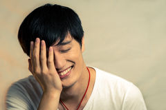 Young man covering his face and smiling royalty free stock photography