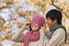 Young Man Covering a Young Woman's Eyes with Hat Royalty Free Stock Image