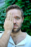 Young man covers half his face by hand. Wide open eyes Royalty Free Stock Photo