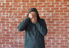 Young man covers his eyes and mouth with hands ,bricks wall as background Stock Images
