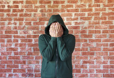 Young man covers his face with hands with bricks wall as background Royalty Free Stock Photo