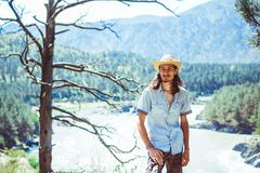 The guy in the cowboy hat. A young man in a cowboy hat against the background of a mountain river Royalty Free Stock Photography