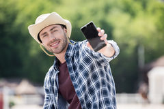 Young man in cowboy hat holding smartphone and smiling at camera. Handsome young man in cowboy hat holding smartphone and smiling at camera Royalty Free Stock Photo