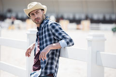 Young man in cowboy hat leaning at wooden fence and looking away Royalty Free Stock Images