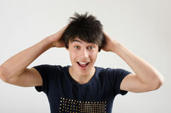 Young man with crazy hair holding his head screaming. Man being happy, amazed and surprised. Royalty Free Stock Images