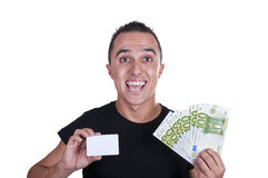 Young man with a credit card and euros. On white background Royalty Free Stock Images