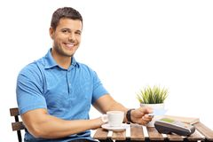 Young man with a credit card sitting at a coffee table Royalty Free Stock Photo