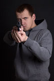 Young man criminal aiming with gun over grey Royalty Free Stock Photo