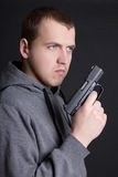 Young man criminal with gun over grey Stock Images