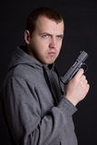 Young man criminal holding gun over grey Royalty Free Stock Image