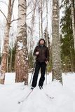Young man cross-country skiing in the forest. Cross-country skiing: man cross-country skiing in the forest in winter Stock Image