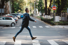 Young man cross the street stock image