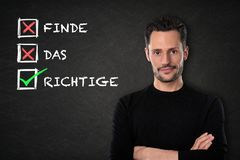 Young man with crossed arms, `Find das Richtige` text on a chalkboard background. Translation: `Find the right one` stock image