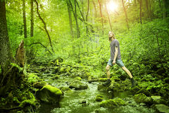 Young man crossing a creek in green forest Royalty Free Stock Image