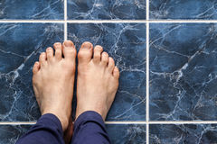 Young man crossing feet on square tiles. Veins in feet visible. Young man crossing feet on square tiles. Veins in feet visible Royalty Free Stock Photo
