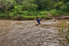 Young man crossing the river on zip line in Chiang Mai. Thailand royalty free stock photo